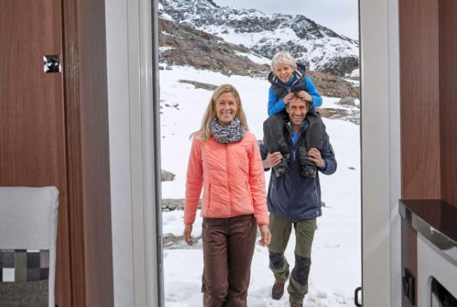A family of 3 stands in the doorway of their RV with snowy mountains behind them