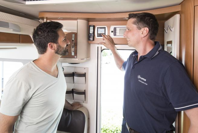 A Truma technician demonstrates the thermostat to a client